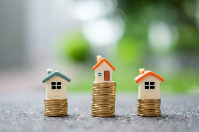 Difference of house model on stack of coins. Decision and Choosing the best Property Investment Concept.